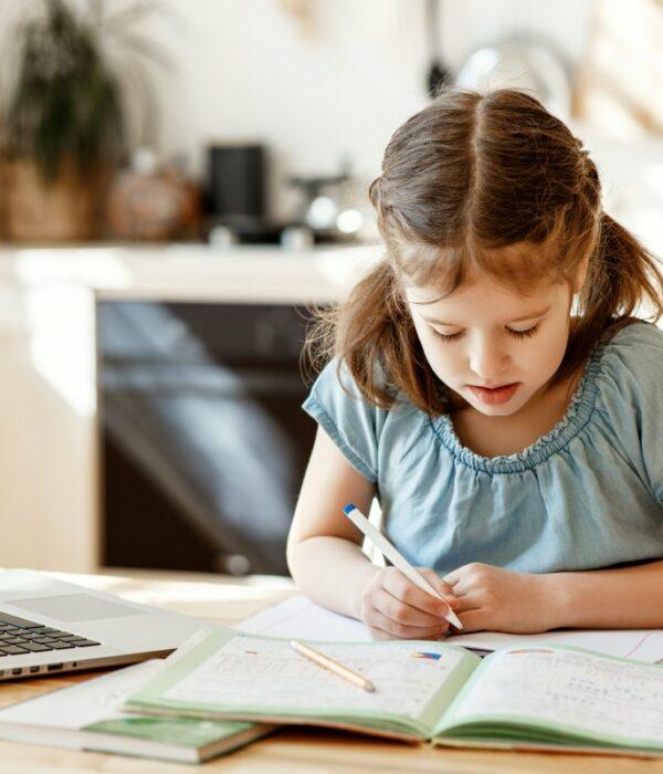 dziewczynka notuje w zeszycie szkolnym leżącym na stole