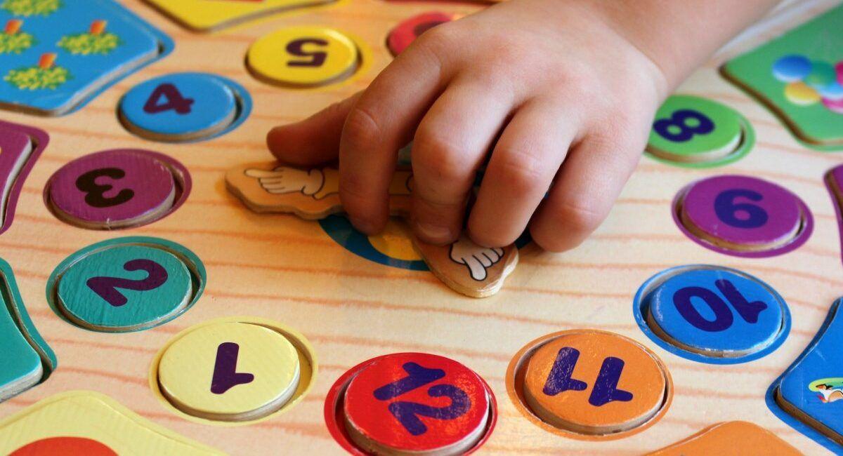 dziecko grające w matematyczną grę planszową