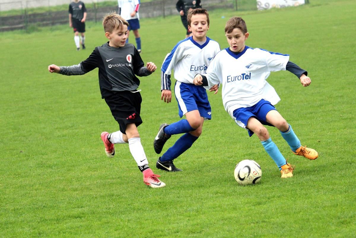 chłopcy grający w piłkę nożną na boisku