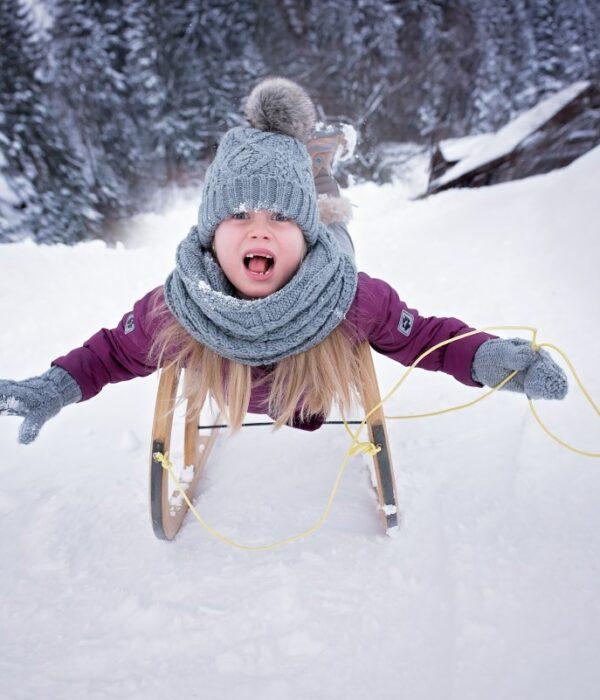 dziewczynka na sankach na śniegu