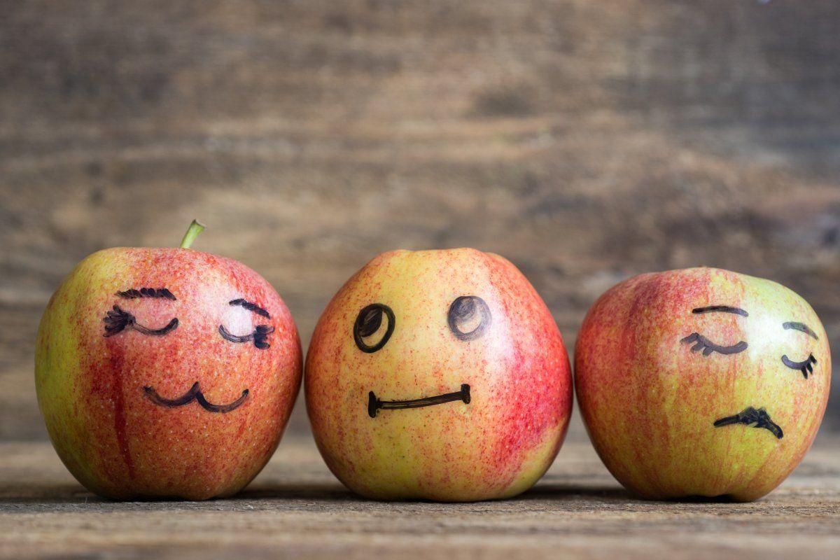 trzy jabłka z narysowanymi buźkami pokazującymi uczucia