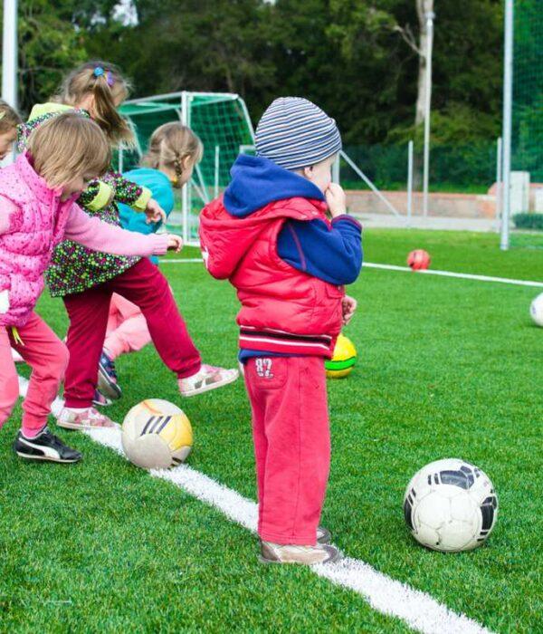 grupa dzieci ćwicząca na boisku sportowym jesienią