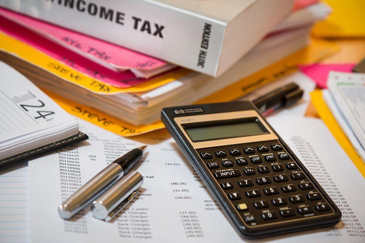 Kalkulator, segregatory, długopis i arkusz z wydatkami leżące na stole. Obliczanie budżetu