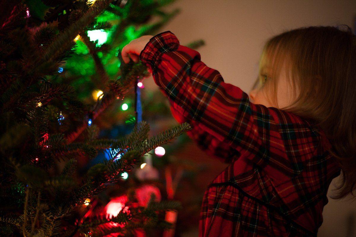 Dziewczynka ubierająca choinkę bożonarodzeniową