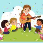 Młoda kobieta gra na gitarze a wokół niej siedzą dzieci i klaszczą lub wystukują rytm